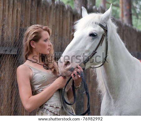 Portrait of lovely young woman with beautiful wavy long hairs and her nice horse on a wooden fence background