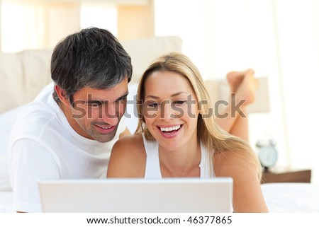 Portrait of lovers using a laptop lying on bed at home - stock photo