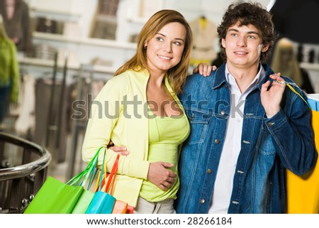 Portrait of loving couple doing shopping and looking at nice clothes in trade center - stock photo