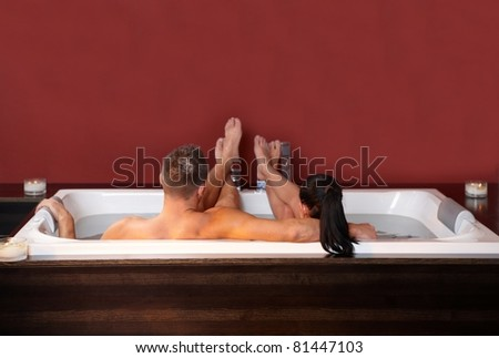 Portrait of loving couple embracing, lying in jacuzzi, relaxing. - stock photo