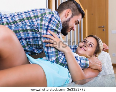 Portrait of loving happy couple on couch at home interior