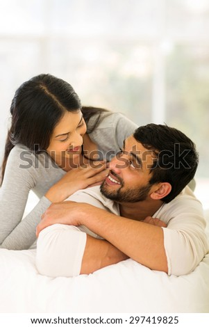 portrait of loving indian couple lying on bed at home
