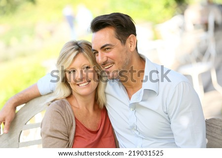Portrait of loving mature couple relaxing on bench