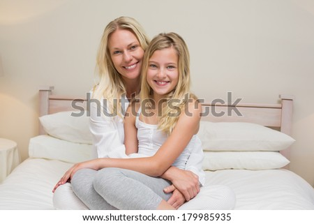 Portrait of loving mother and daughter sitting on bed at home