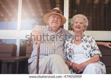 Portrait of loving retired couple relaxing on a bench outside their house. Caucasian elderly man and woman sitting relaxed on a bench outdoors.