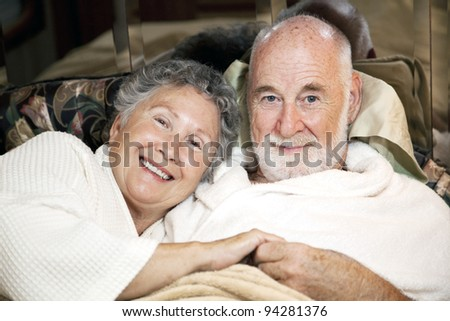 Portrait of loving senior couple in bed together. - stock photo