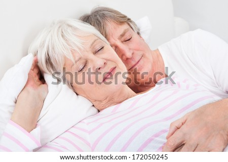 Portrait Of Loving Senior Couple Lying On Bed - stock photo