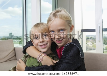 Portrait of loving siblings in dinosaur and vampire costumes at home - stock photo