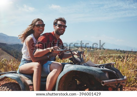 Portrait of loving young couple cruising over country roads by quad vehicle. Happy man and woman driving a quad bike. - stock photo