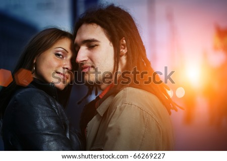 Portrait of loving young couple in city at sunset - stock photo