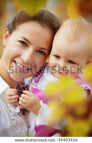 Portrait of loving young mother holding her baby in autumn park - stock photo