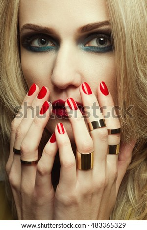 Portrait of luxurious blonde model. Perfect hair, skin, make-up, manicure. Golden accessories. Close up