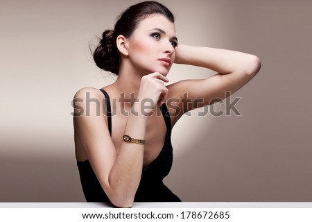 Portrait of luxury woman in exclusive jewelry watch on natural background - stock photo