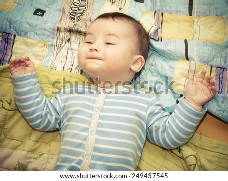 Portrait of lying caucasian baby boy at home - stock photo