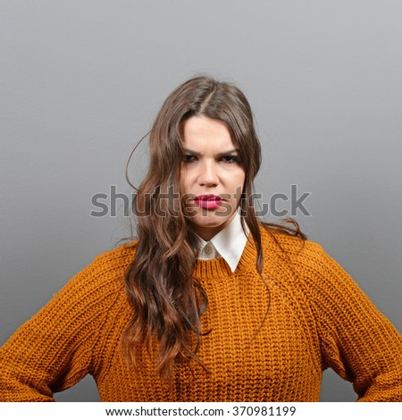 Portrait of mad woman against gray background - stock photo