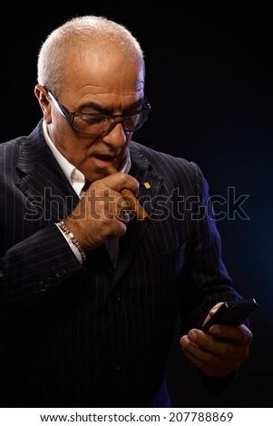 Portrait of maffia boss smoking cigar, using mobilephone. - stock photo