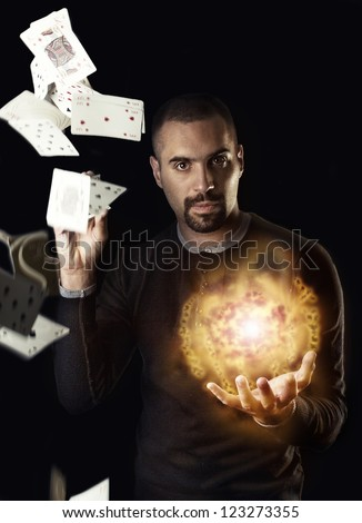 Portrait of magician with magic lighting ball and cards
