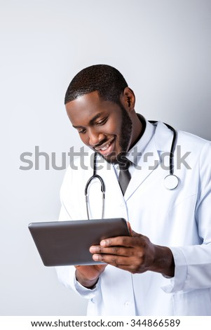Portrait of male afro american doctor with stethoscope and lab coat. Young doctor smiling and using tablet computer. Man standing on grey background