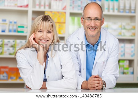 Portrait of male and female pharmacists leaning on pharmacy counter - stock photo