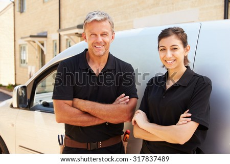 Portrait of male and female trade workers standing by a van - stock photo