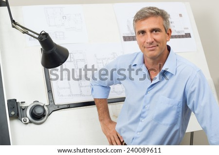 Portrait Of Male Architect With Blueprint At Office - stock photo