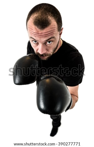 Portrait of male athlete boxer man looking aggressive with boxing gloves on, black shirt and tattoos. Isolated on white background. Man self defense. - stock photo
