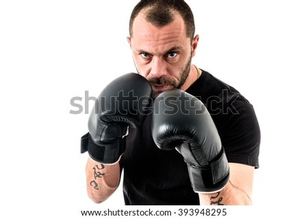Portrait of male athlete boxer man looking aggressive with boxing gloves on, black shirt and tattoos. Isolated on white background - stock photo