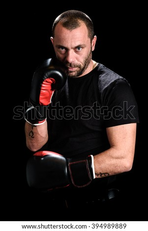 Portrait of male athlete boxer man looking aggressive with boxing gloves on, black shirt and tattoos. Isolated on black background - stock photo