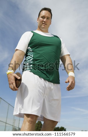 Portrait of male athlete holding discus against sky - stock photo