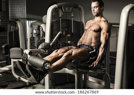 Portrait of male bodybuilder doing exercise at gym - stock photo