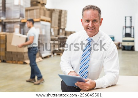 Portrait of male boss using digital tablet in warehouse