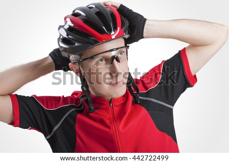Portrait of Male Caucasian Cyclist Posing in Red Road Protective Helmet and Glasses. Against White Background. Horizontal Shot - stock photo