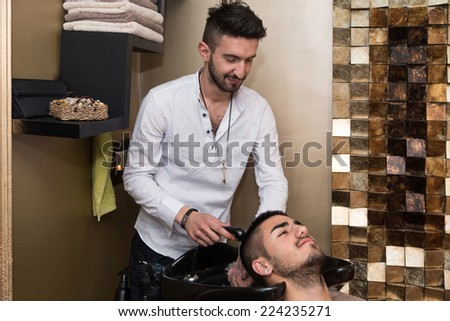 Portrait Of Male Client Getting His Hair Washed - Hairstylist Hairdresser Washing Customer Hair - Young Man Relaxing In Hairdressing Beauty Salon - stock photo