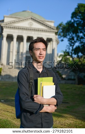 portrait of male college student holding book with bag at campus - stock photo