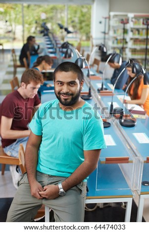 portrait of male college student sitting on table in library and looking at camera. Vertical shape, high angle view