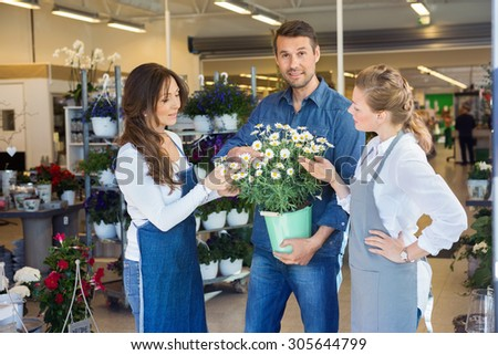 Portrait of male customer being assisted by salesgirls in buying flower plants at store - stock photo
