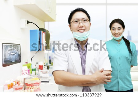 Portrait of male dentist and his assistant in the dentist clinic - stock photo