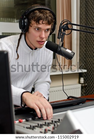 Portrait of male dj working in front of a microphone on the radio - stock photo