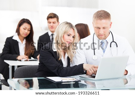 Portrait of male doctor and businesswoman with laptop sitting at desk in office - stock photo