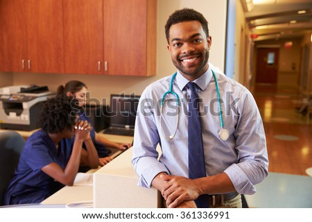 Portrait Of Male Doctor At Nurse's Station In Hospital - stock photo