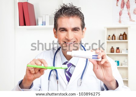 Portrait of male doctor holding tooth brush and toothpaste. - stock photo