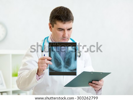 Portrait of male doctor reviewing x-ray with clipboard at office - stock photo