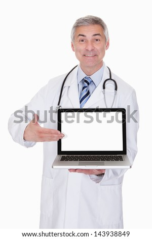 Portrait Of Male Doctor Showing Laptop Over White Background
