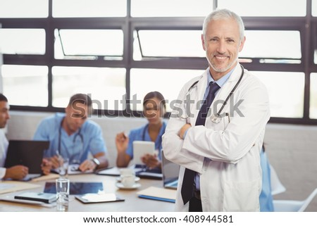 Portrait of male doctor standing with arms crossed and colleagues discussing in background - stock photo