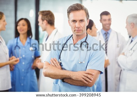Portrait of male doctor standing with arms crossed and colleagues standing behind and discussing in hospital - stock photo