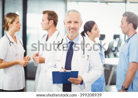 Portrait of male doctor writing on clipboard and colleagues standing behind and discussing in hospital