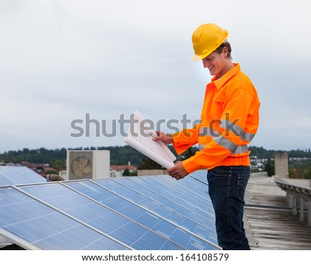 Portrait Of Male Engineer Holding Blueprint Standing In Front Of Solar Panel - stock photo