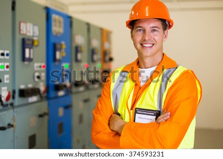 portrait of male engineer with arms folded in power plant control room