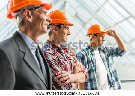 Portrait of male engineers builder in yellow helmet in the office center - stock photo