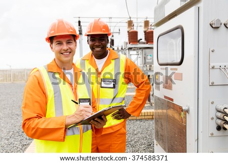 portrait of male engineers working together in electrical substation - stock photo